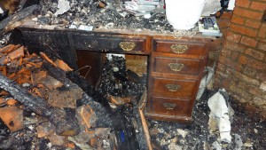 Burnt antique desk. Flood or fire damage valuations are offered by Malcolm Green Valuations.
